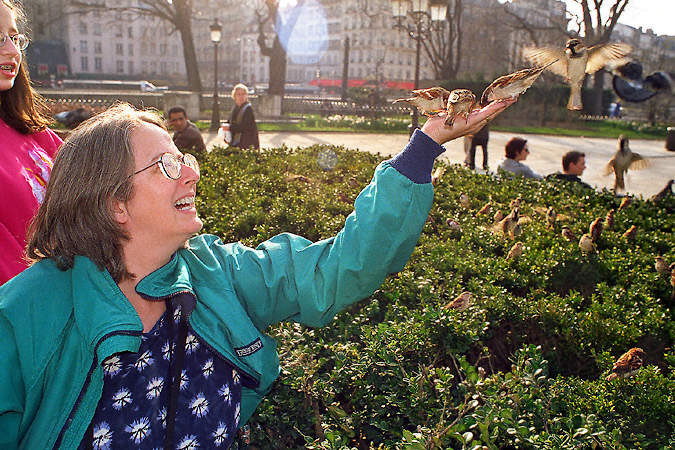 An American Tourist Feeding Birds In Front Of Notre Dame