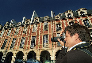 A photography student looking at place des Vosges through the viewfinder of his camera.