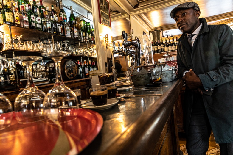 A man at the bar inside the café Louis-Philippe on rue de l'Hôtel de Ville