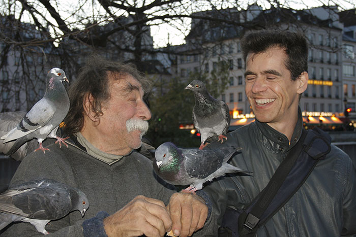 Pierre Pradeau and David Henry with pigeons in front of Notre-Dame.